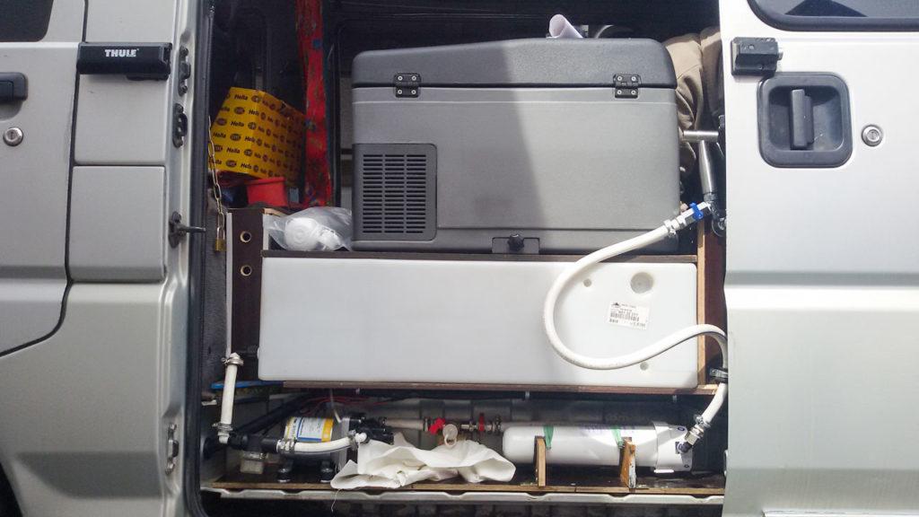Das Druckwassersystem mit Filteranlage. Links unten die Wasserpumpe, rechts unten der Filter mit Schlauch zur Amatur und dazwischen der Anschluss für die Dusche. Darüber ist der Wassertank
